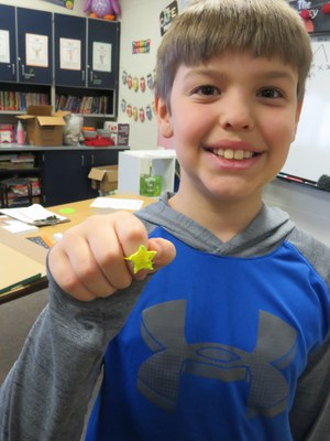 A 4th-grade student shows off the star-shaped ring he made using the 3Doodle pen.