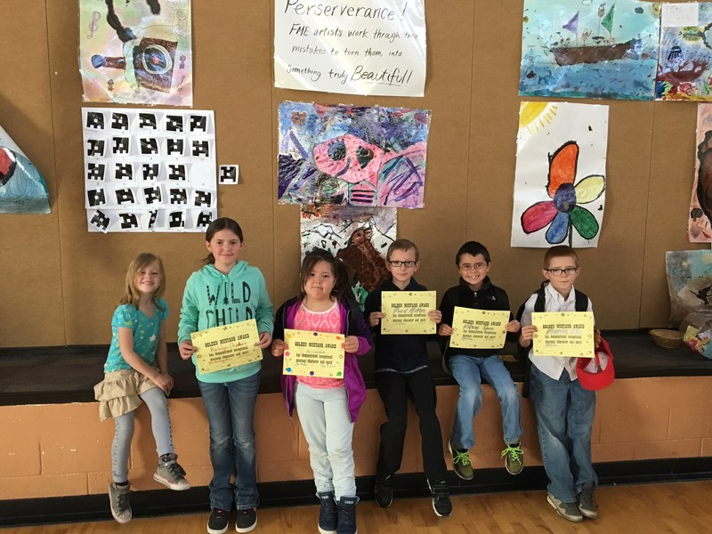 Students hold their gold mustang awards.