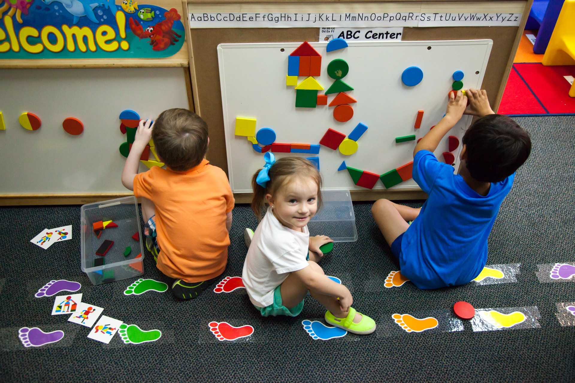 Three elementary students learn their colors and shapes by using the classroom's magnetic whiteboard