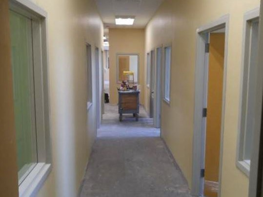 Hallway with yellow and green walls and a cart of construction materials