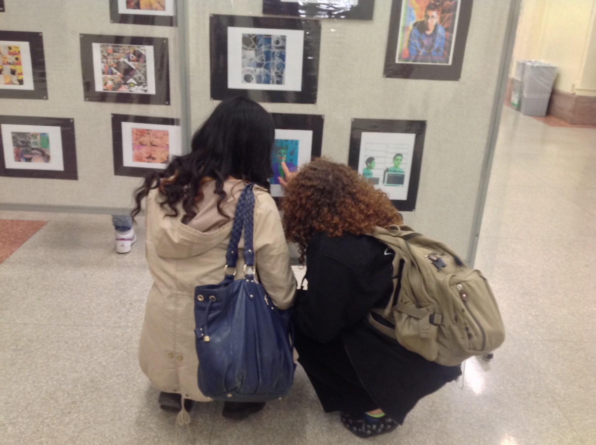 Students looking at artwork at exhibit.