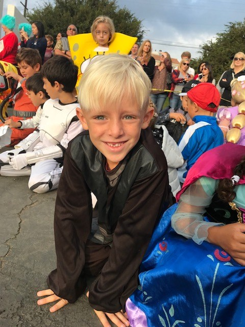Student sitting during Halloween parade in batman costume.