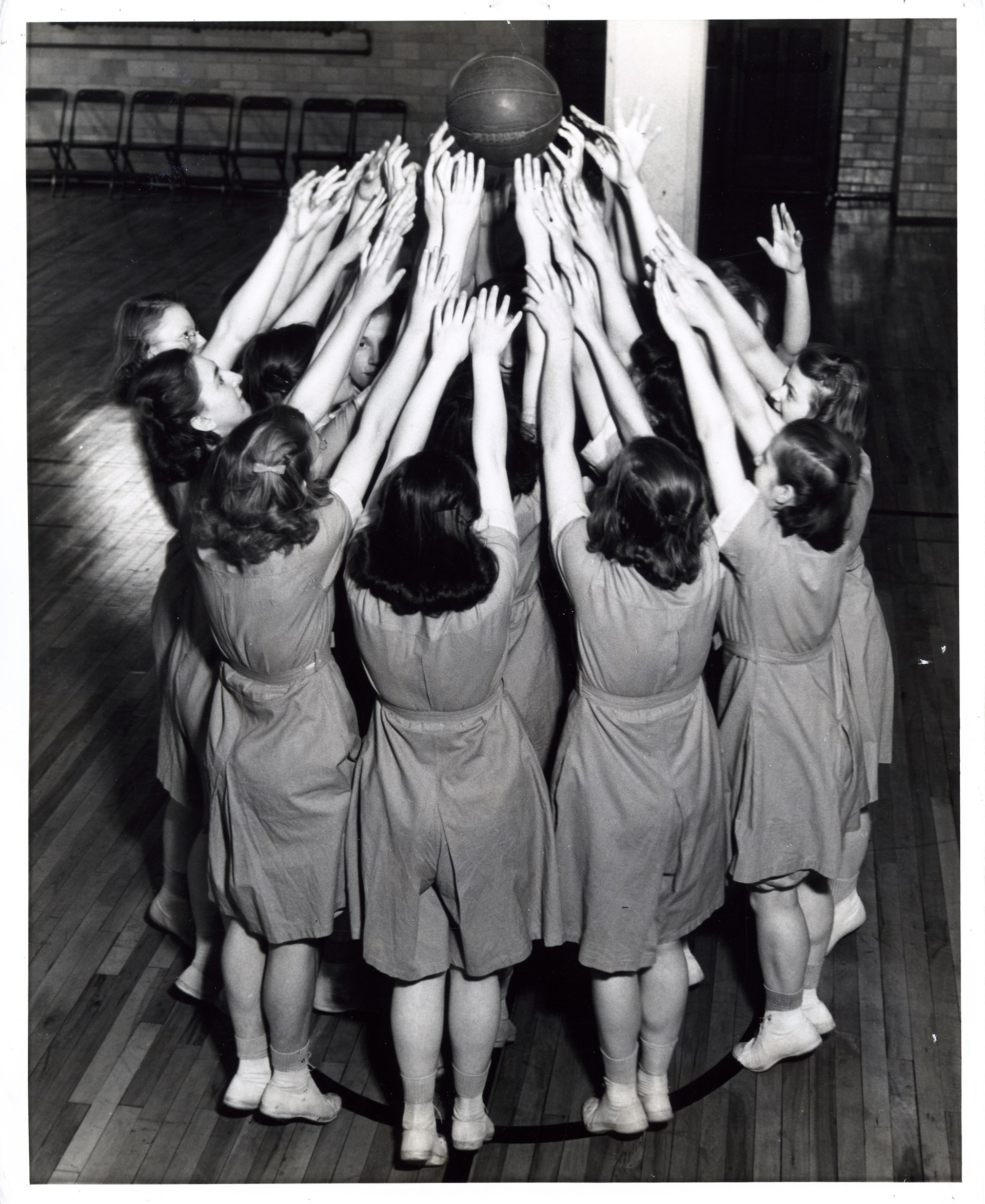 A group of young women pose with arms up in the air around a basketball