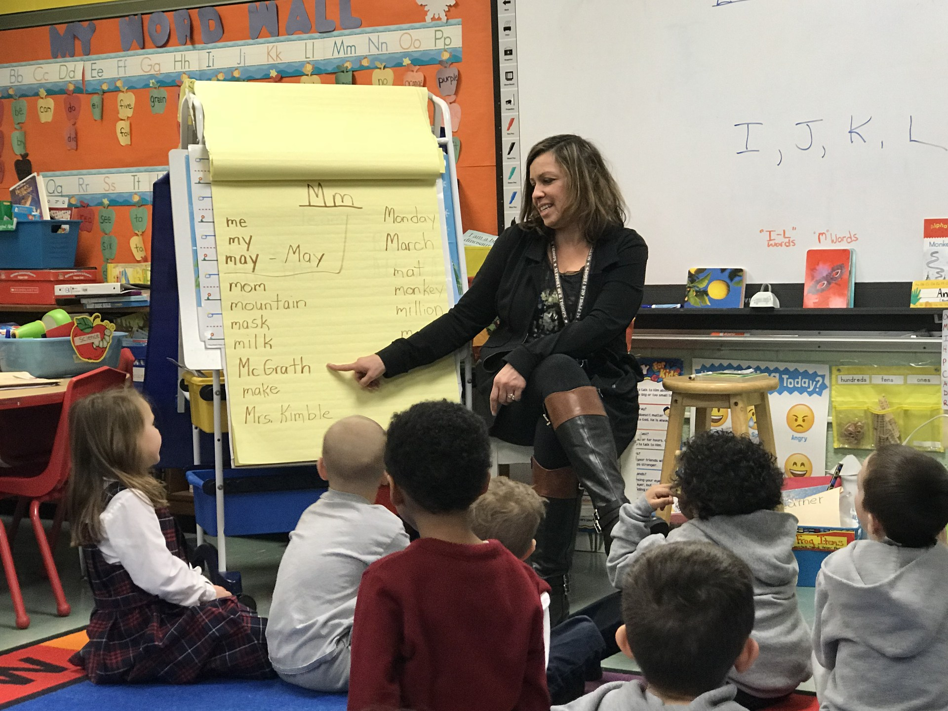 Pre-Kindergarten teacher showing students how to spell words