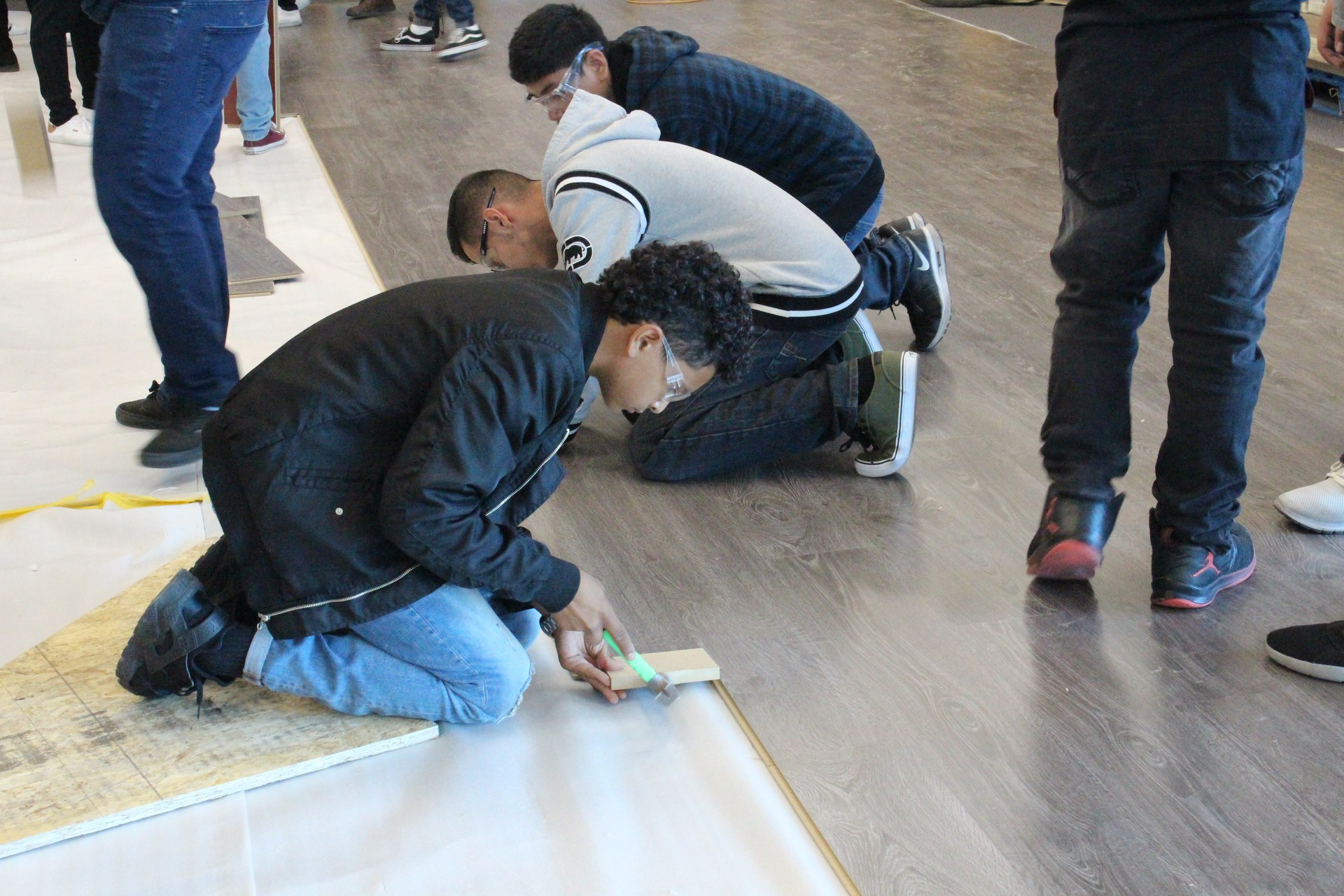 Students installing the new floor in the Tech Center