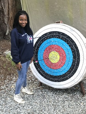 a student posing next to archery target