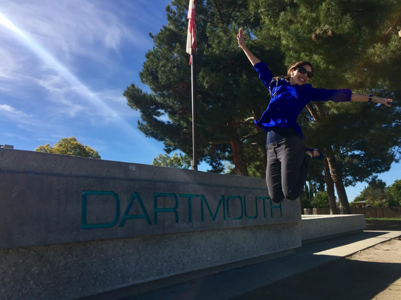 Nilma Alvarez-Drinkwater jumping in front of a Dartmouth Middle School sign.