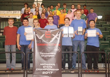 RoboDawgs team stand in bleachers with VEX sign