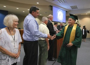 Board Member Joe Wojik shaking hands with a graduate.