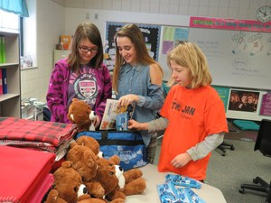 Students work together to fill the duffel bags with toiletries, coloring books and a stuffed teddy bear.