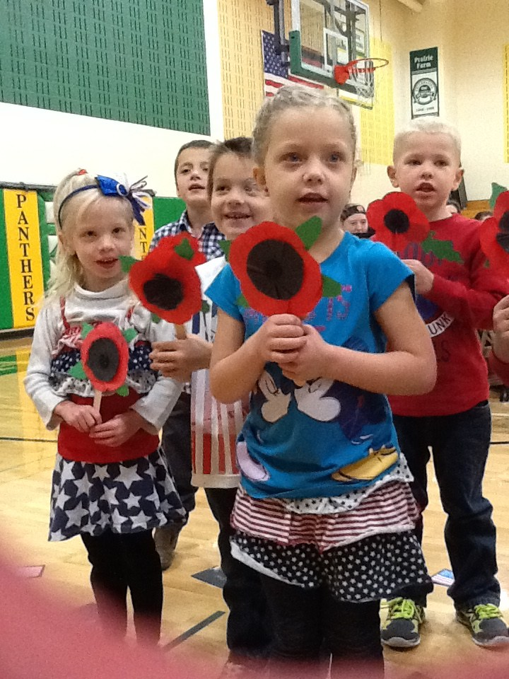 Students holding paper poppies.