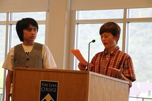 Students speak at a podium at the Great Brains Expo.