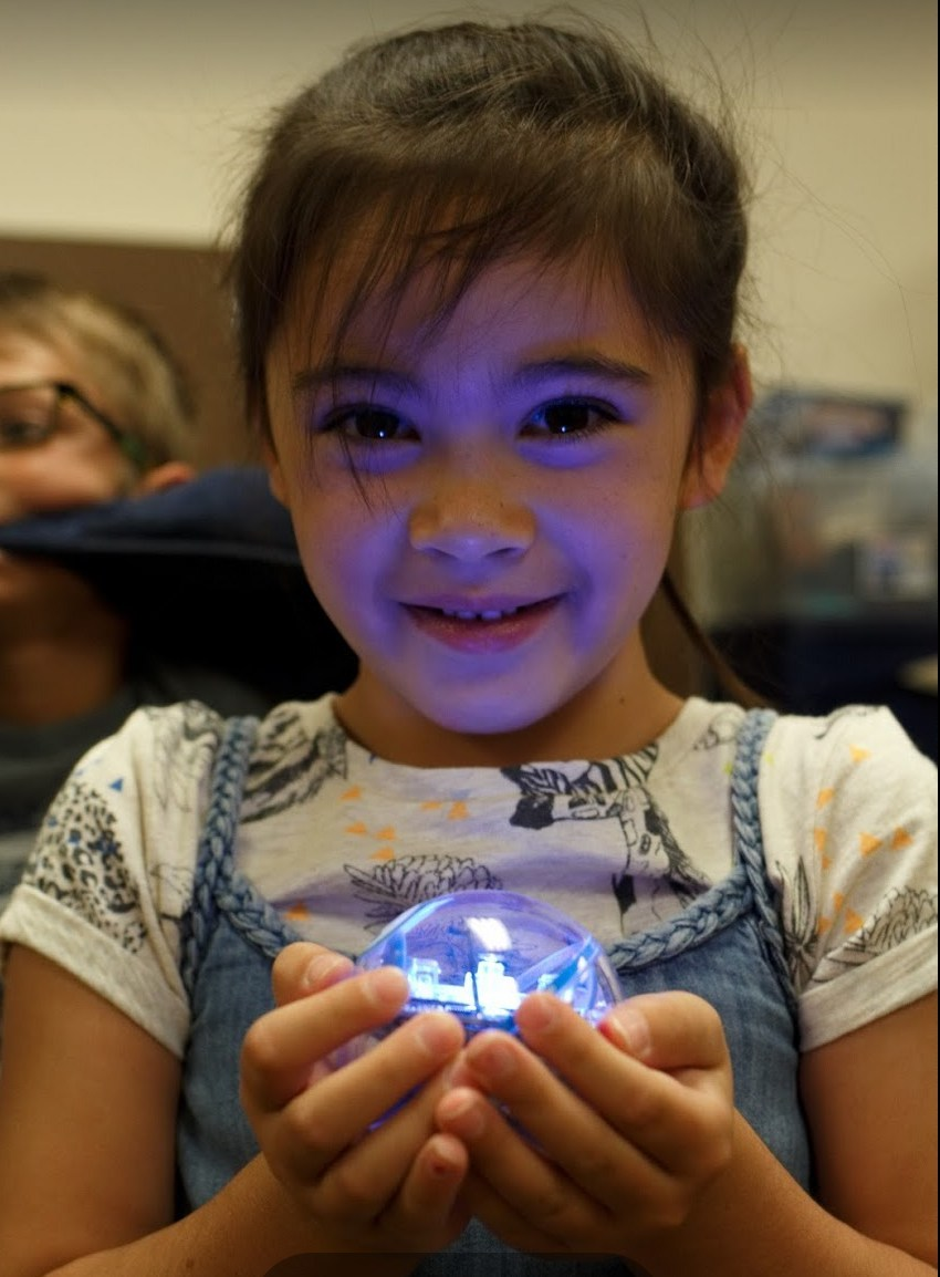 elementary girl holding an orb