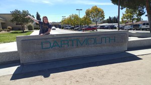 Debbie Pease in front of a Dartmouth Middle School sign.