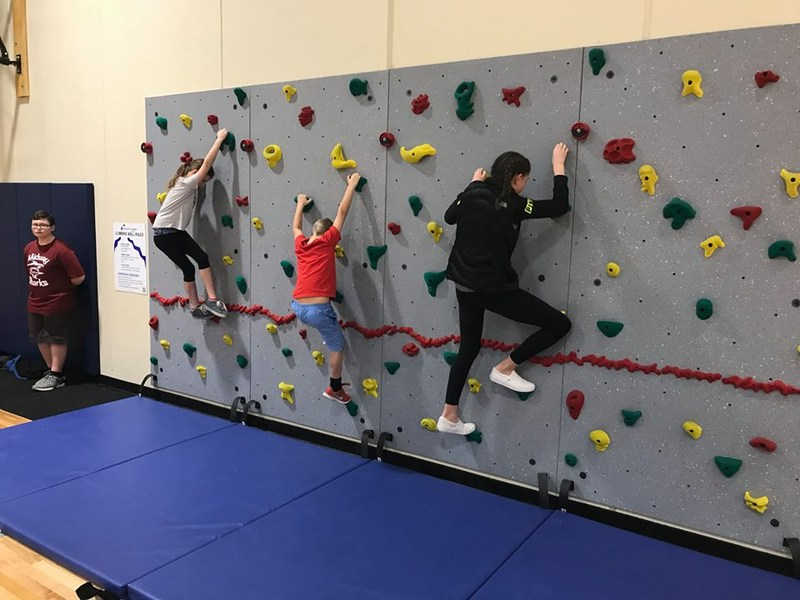 Students try out the new climbing wall in the Midway gym.