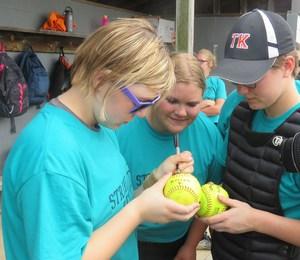 TK JV softball team members autograph balls for honored cancer survivors.