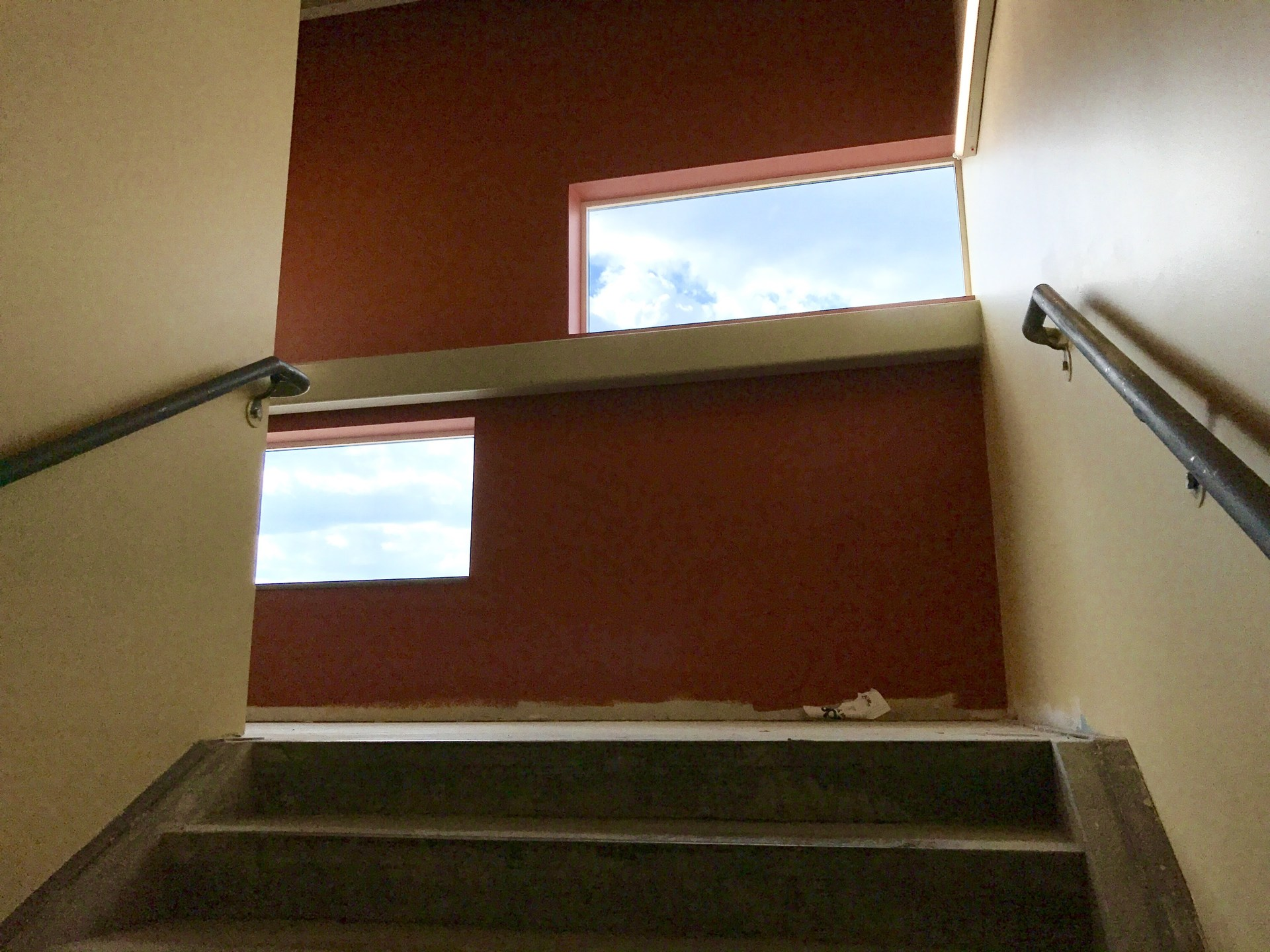 Stairwell with a red wall and windows showing blue sky