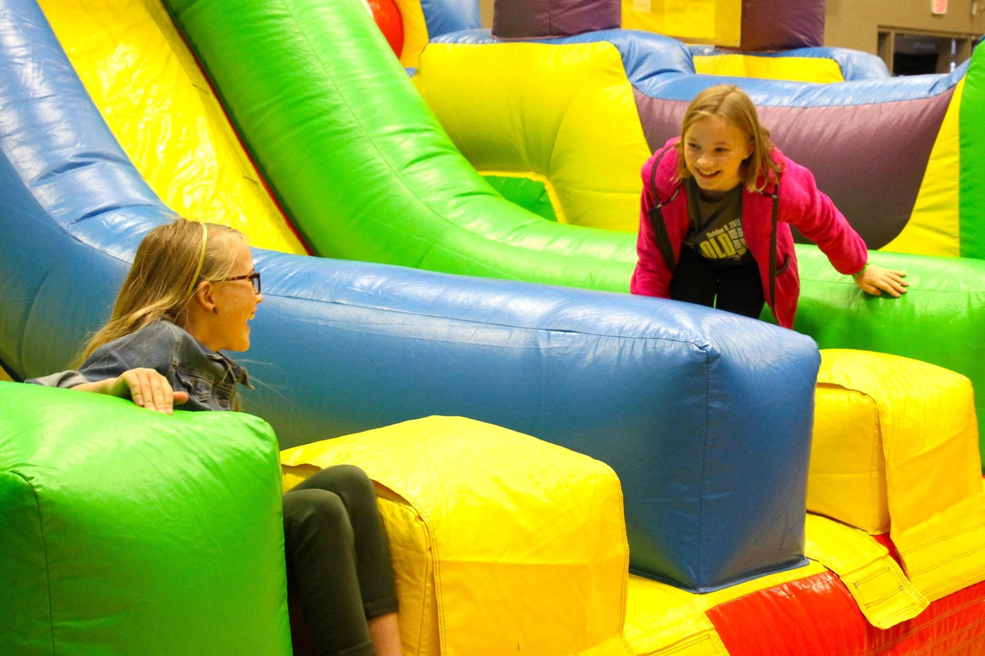 kids smiling at the bottom of bouncy slide