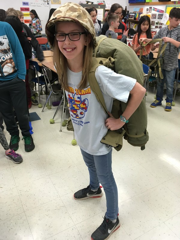 Student tries on the WWII backpack
