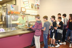Students wait in line to get lunch in the cafeteria.