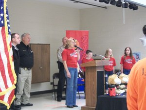 Principal, DARE officer, students, and others are standing on stage.