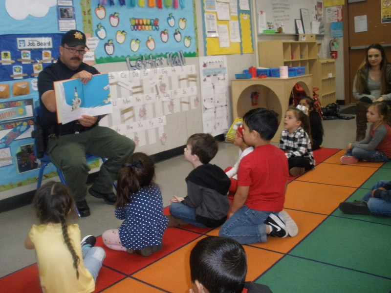Officer Vargas reading to Aileen Colburn preschool students