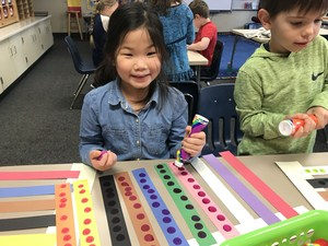 Students put 10 dots on 10 strips of paper to count to 100.