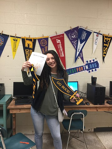 female student smiling and holding a college acceptance letter