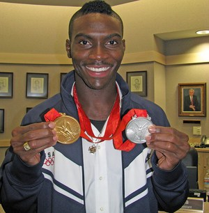 Clement holding a gold medal and silver medal