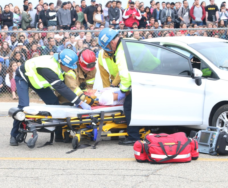 Fire fighters pulling a student from a car
