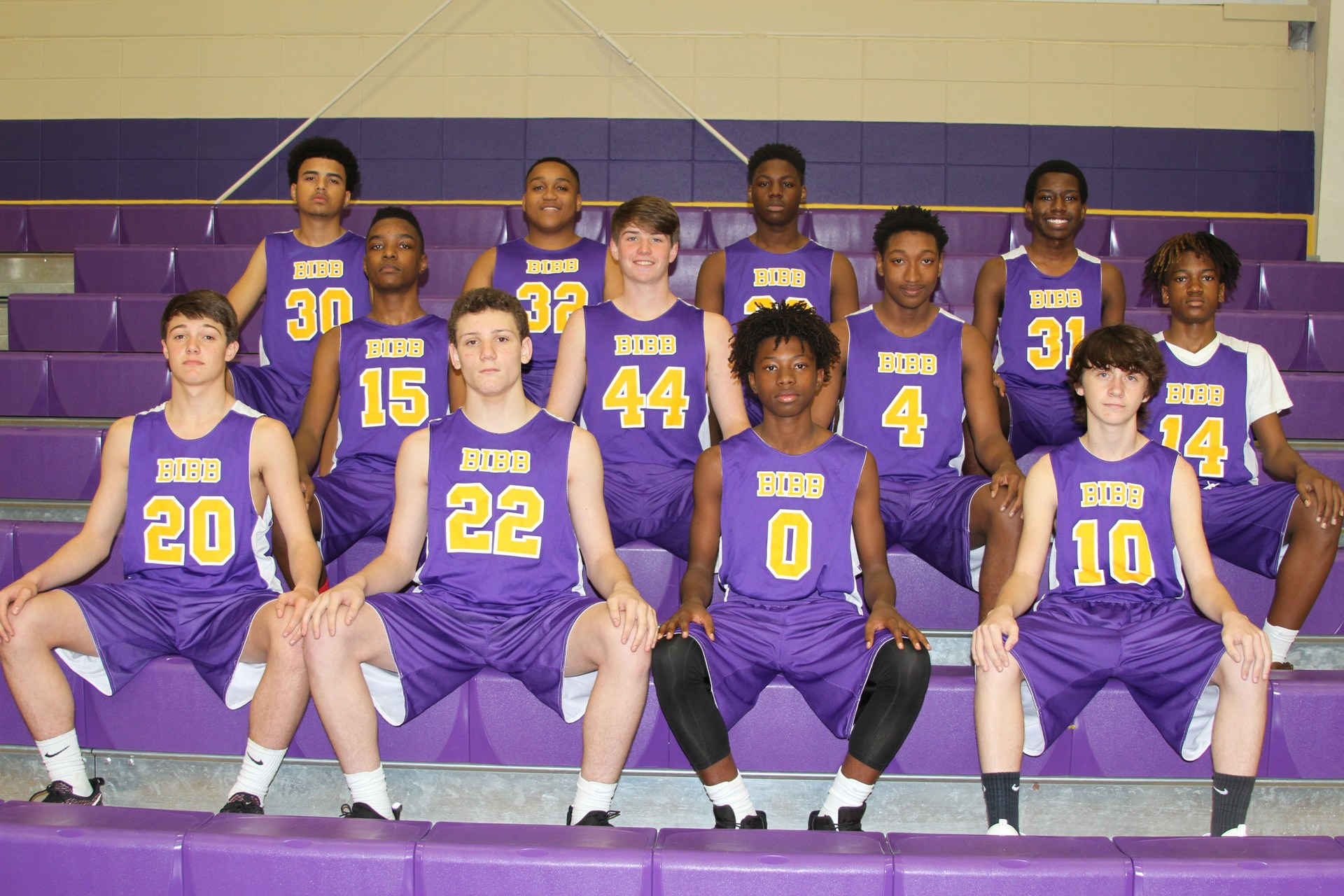 Bibb County High School Basketball players in uniform seated on bleachers in the gym