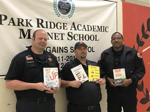 a photo of 3 members of the Baker Fire Department holding a book in hallway at Park Ridge for national reading day ..