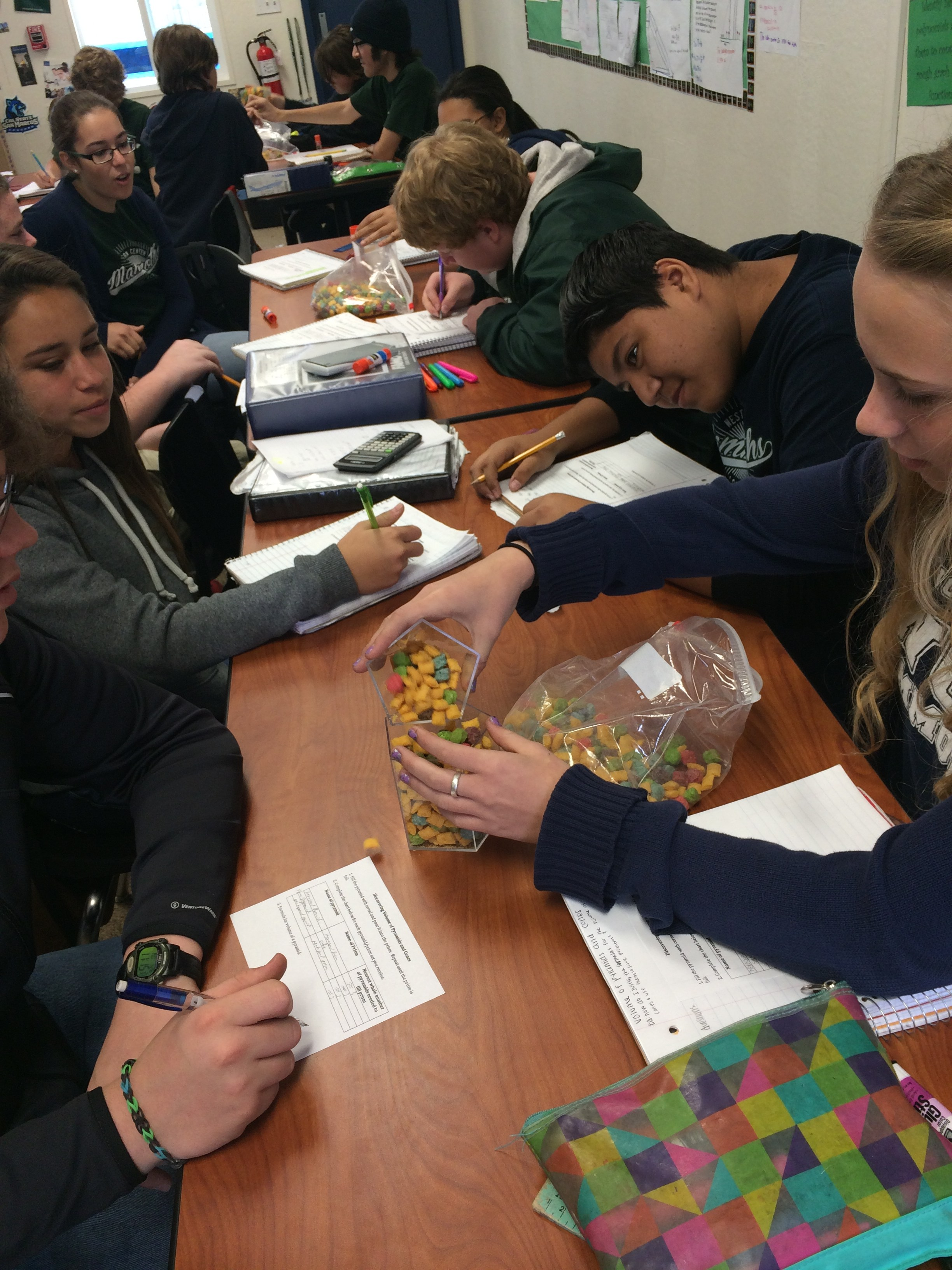 students are using cereal to derive the formula for the volume of a pyramid