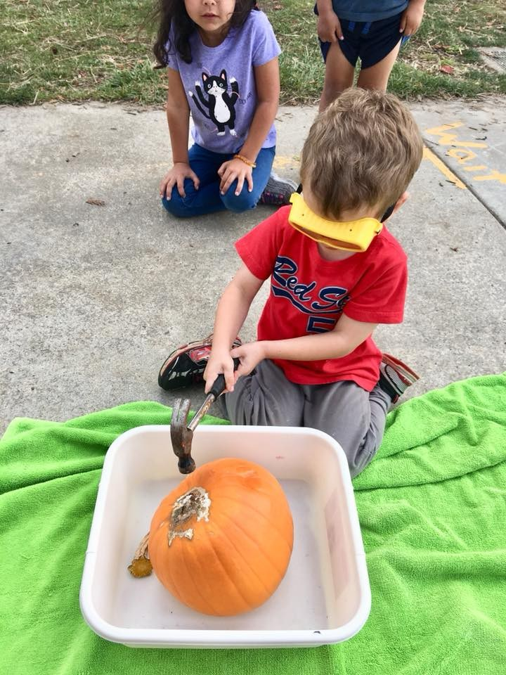 Young child wearing safety goggles and exploring a pumpkin