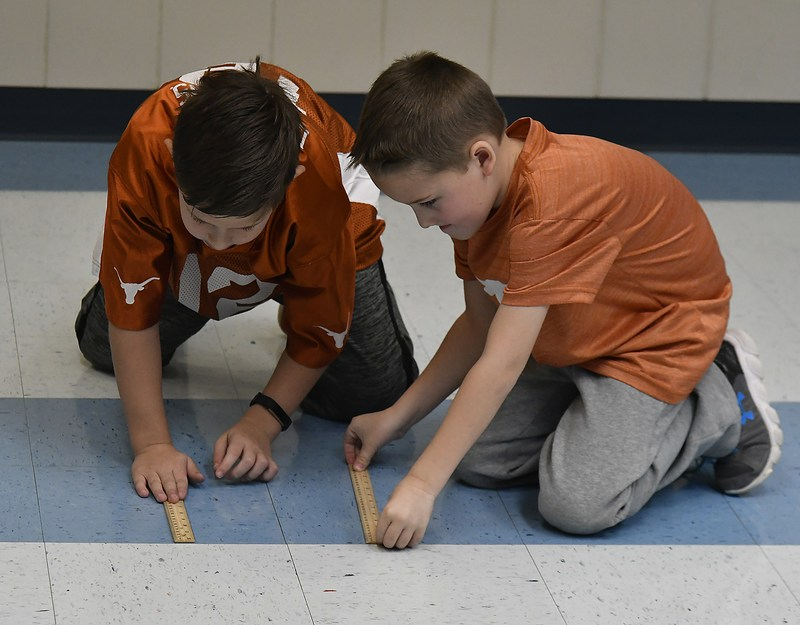 Lillian Elementary second graders Aiden Higgins and Cole Nors measure how far their discus flew during the Measurement Olympics.