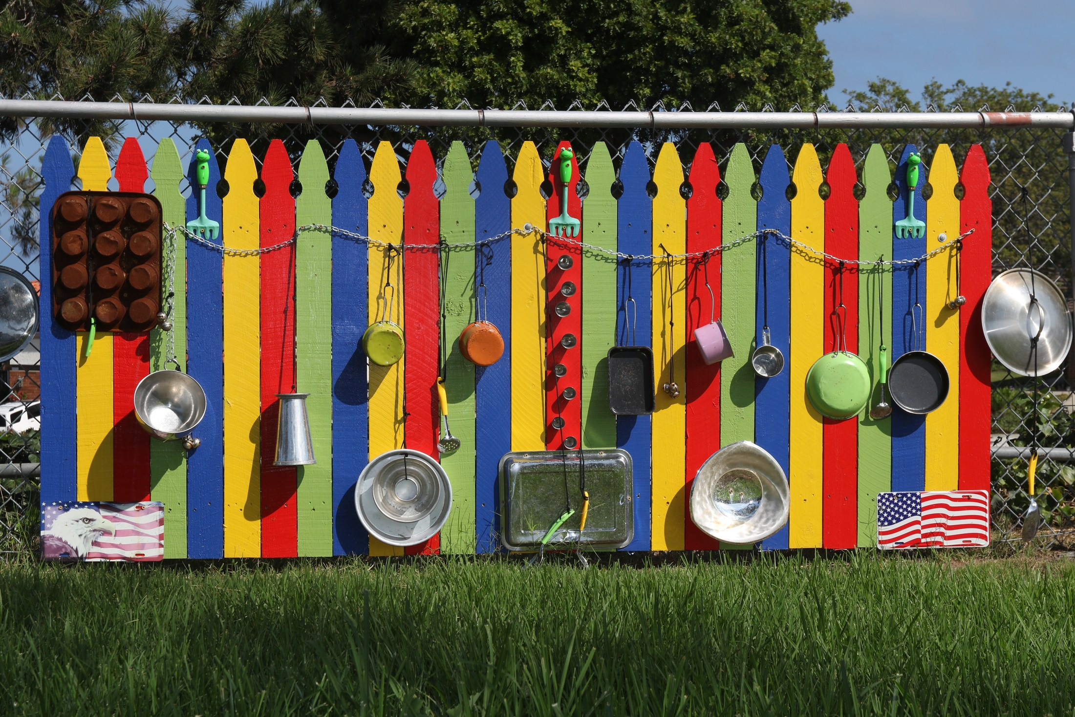 multi-colored fence with playthings attached