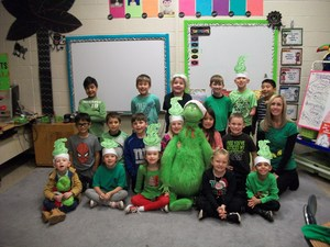 First grade class of students with a stuffed Grinch.