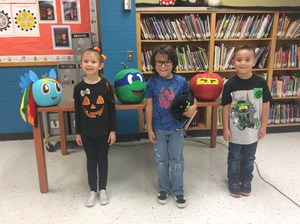 Students posing with their pumpkins in the library.