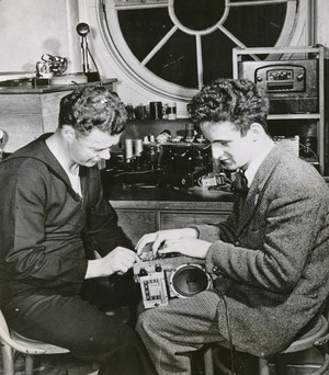 A student and veteran looking at radio equipment