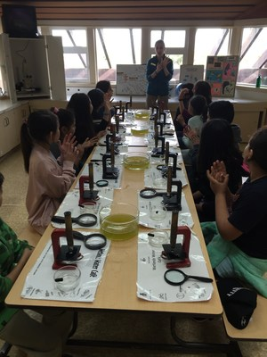 Students in a lab looking at marsh water through microscopes