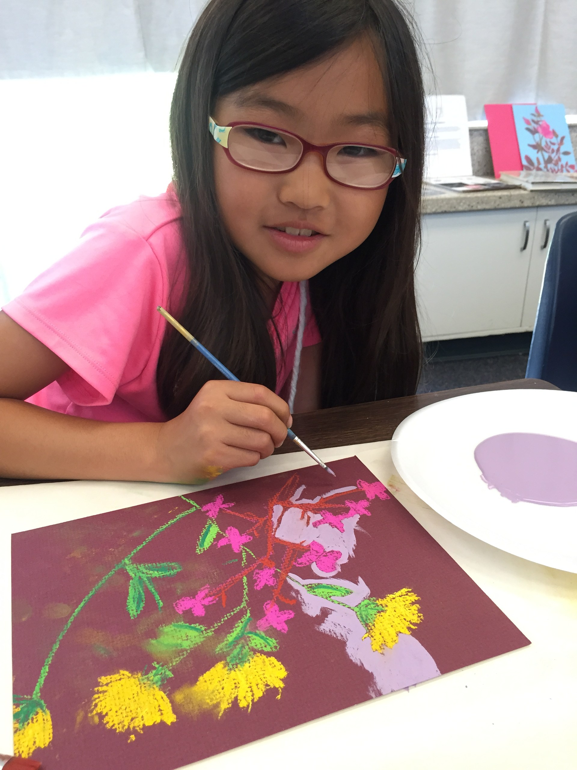 Girl painting a picture of flowers.