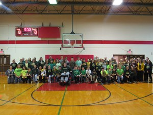 Large group photo of middle school students and staff gathered in gymnasium