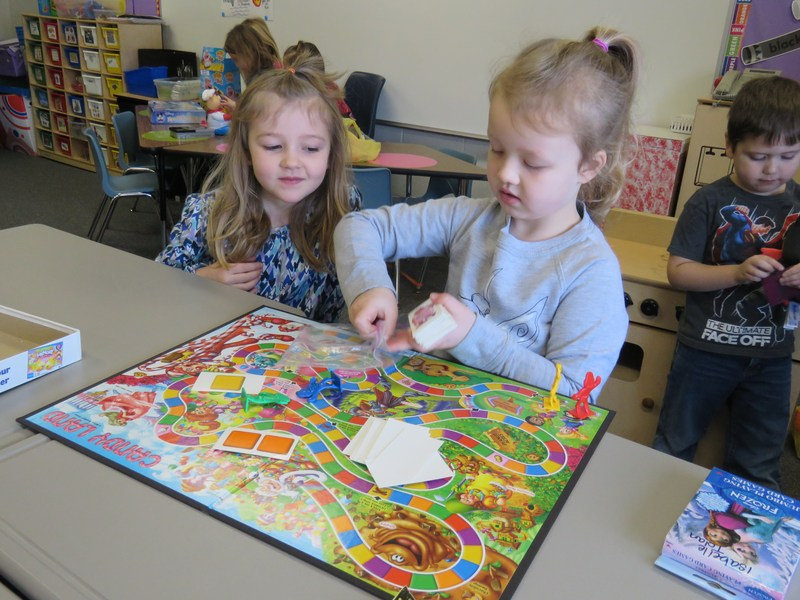 Two kindergarten students set up a game of