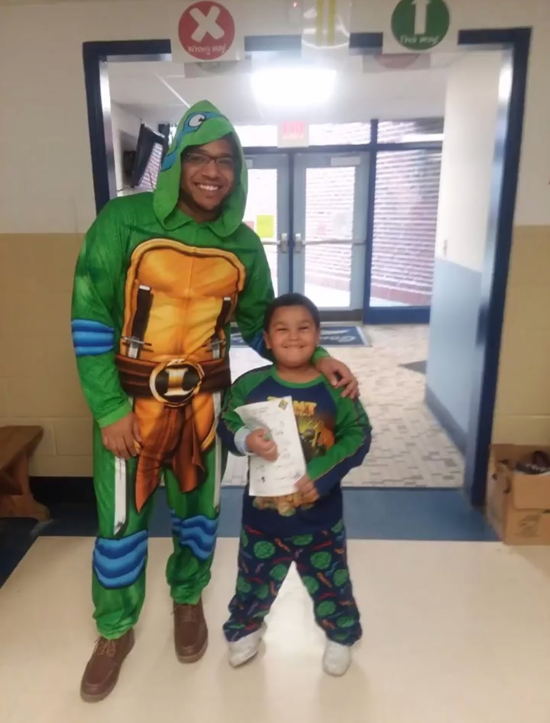 Mr. Smith with a young 5 student on pajama day.