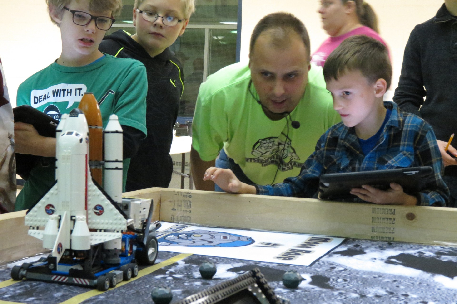 Mr. Miller works with two students on their robot at the final challenge.