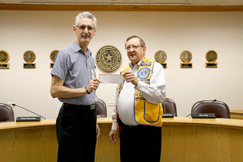 Picture of check presentation to district representative by Lions Club