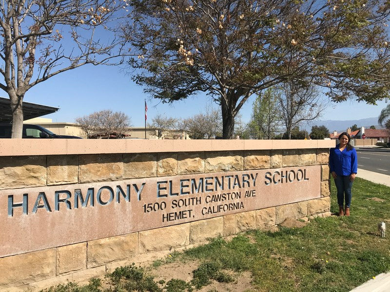 Crystal Rodarte standing in front of a Harmony Elementary sign.