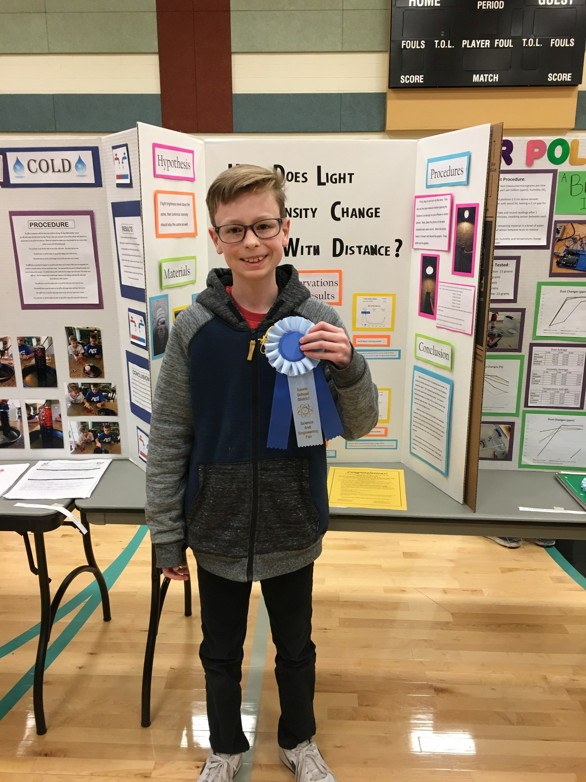 Boy holding his ribbon in front of his Science Fair Project