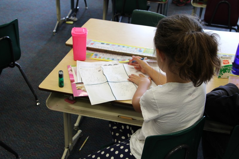 Student writing at her desk.