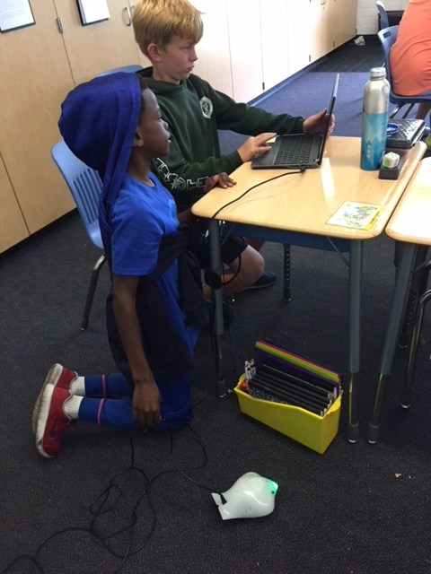 Two boys programing a robot.